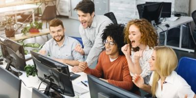 Cheerful emotional team enjoying victory, reading winning results on computer monitor in office, empty space